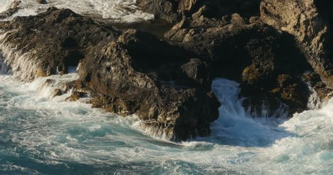 4K, Dramatic water waves splashing and crashing against rocks