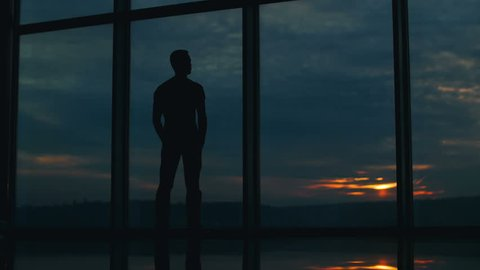 The man stands by sky scraper business center windows by sunset background. Time lapse footage