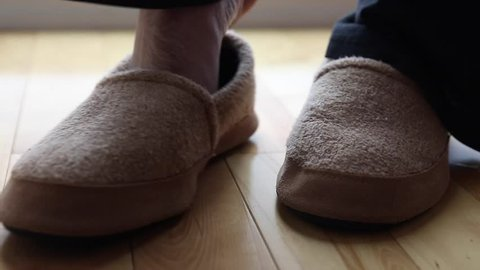 a man wears a pair of slippers dolly shot