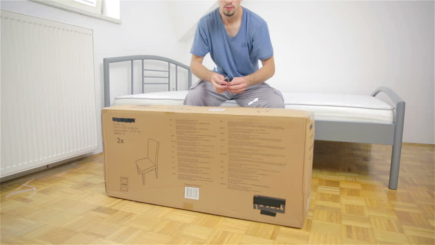Man cutting big thin box with knife  Person buys new furniture elements for  new home. Cutting Box On Floor  Person Buys New Furniture Elements For New