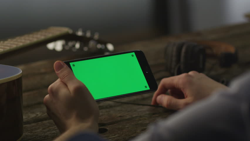 Musician Using Phone in Landscape Mode at Home. Causal Lifestyle. Great for Mock-up, most popular gestures used. Shot on RED Cinema Camera in 4K (UHD). ProRes codec  - Great color correction. | Shutterstock HD Video #8577613