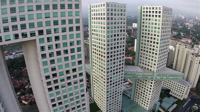 Aerial shot and close up of a big building at the Corporate Zone in Santa Fe in Mexico City with big buildings on the back