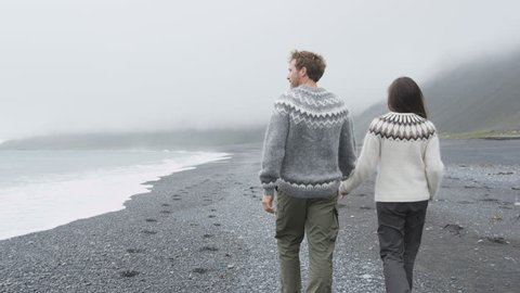 Couple walking on beach holding hands on Iceland. Romantic couple walking wearing Icelandic sweater on black sand beach from behind showing rear view of back. Tracking steadicam with RED EPIC 60 FPS.