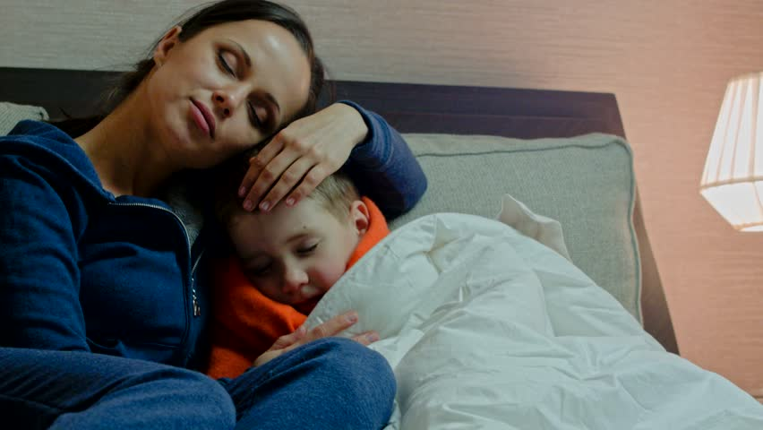Young mother and her sick son in bed