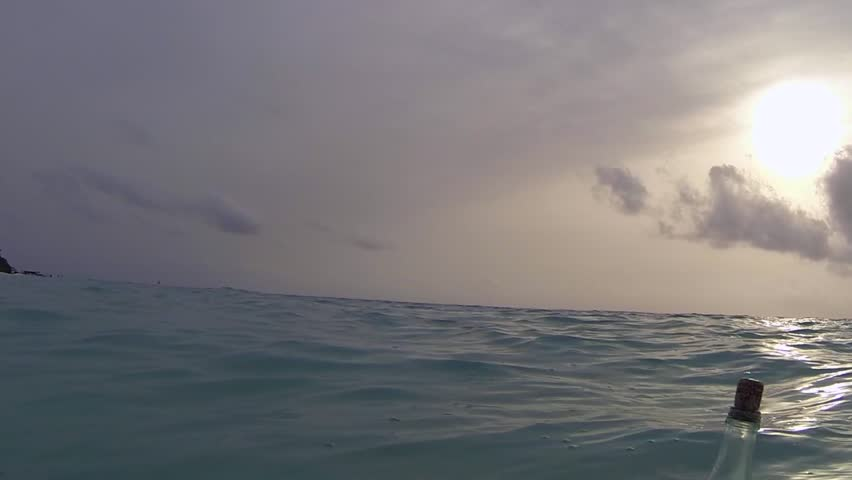 A floating, corked but empty bottle viewed from sea level in the Indian Ocean near Maldives as it bobs past at sunset. Possible metaphor for sea level rise due to climate change.  Camera is handheld.