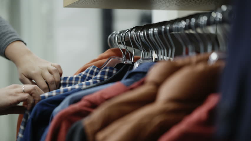 Woman in the shop looks through the male jackets and shirts, which are hanging on the racks
