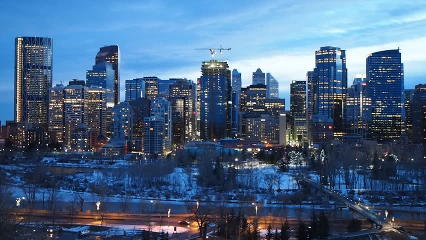 Calgary skyline at night with Bow River in the foreground.