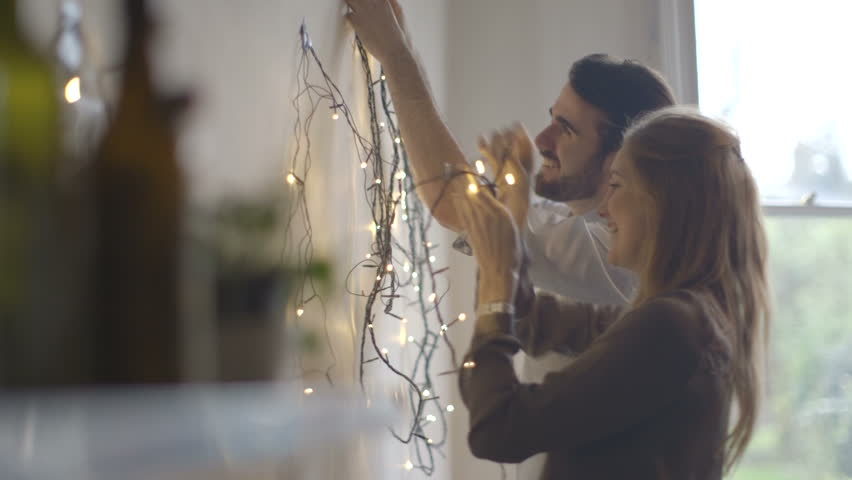 Young man and woman decorating wall with fairy lights | Shutterstock HD Video #8685973