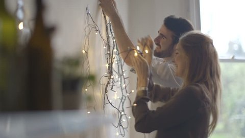 Young man and woman decorating wall with fairy lights
