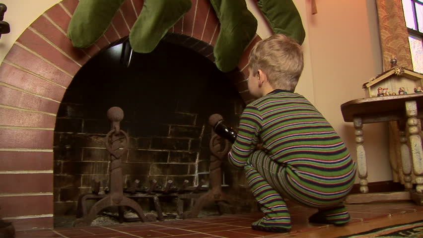 Toddler in pajamas looking for Santa in the fireplace at Christmas