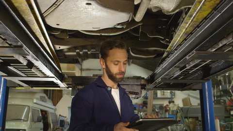 Mechanic inspects the car undercarriage way with a digital tablet
