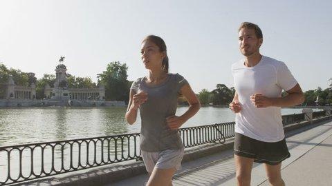 Sport runners jogging running in Madrid El Retiro city park. Exercising woman and man runner training on jog living healthy lifestyle in Buen Retiro Park, Parque el Retiro in Madrid, Spain, Europe.