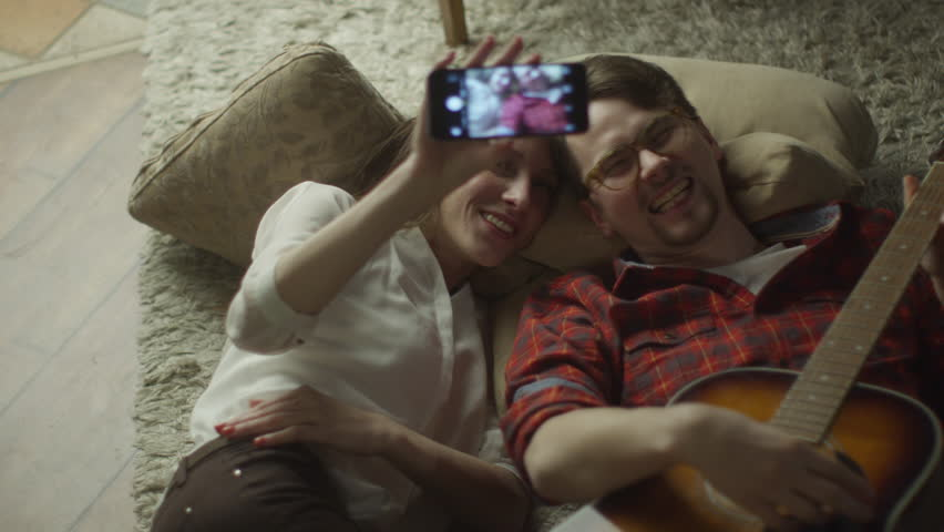 Young Happy Smiling Couple are Lying on the Floor and Doing Selfie with Mobile Phone at Evening at Home. Casual Lifestyle. Shot on RED Cinema Camera in 4K (UHD). ProRes codec  - Great for editing.