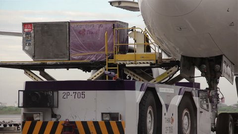 BANGKOK, THAILAND, JANUARY 2015: Baggage handlers ready to load cargo on a Thai Airways International plane at Suvarnabhumi Airport, Bangkok, Thailand.