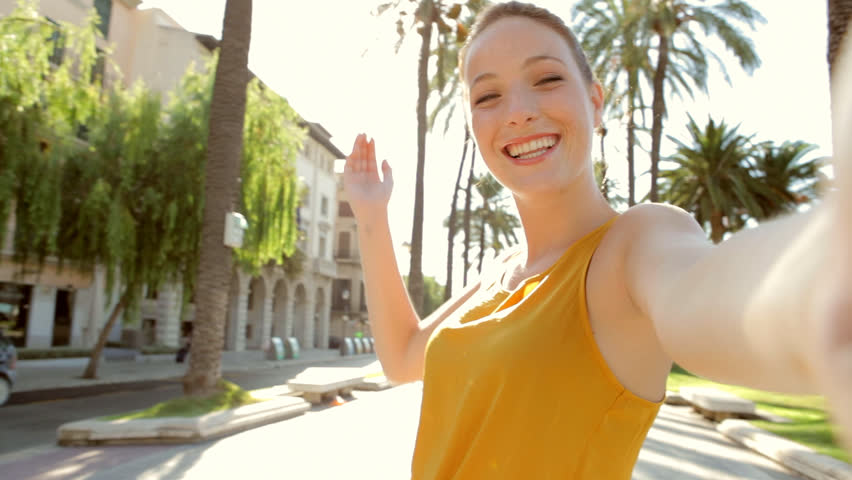 Portrait of attractive young tourist woman visiting a destination city on holiday, holding a video camera and filming herself like in a selfie, networking on vacation. Travel and technology lifestyle. | Shutterstock HD Video #8814313