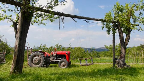Old red tractor parked in a green courtyard with a swing swinging in front in a slow motion.