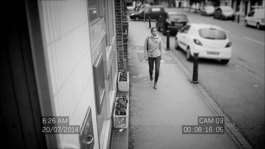 4K CCTV footage of suspicious male following a woman who has just taken cash from an ATM machine