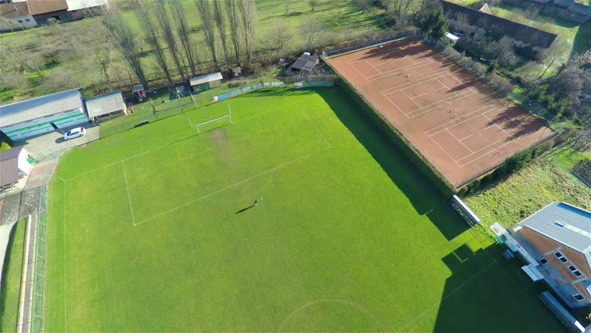 Aerial 4K descending on soccer player on empty field. High above the soccer green field with one person training, kicking on goal.