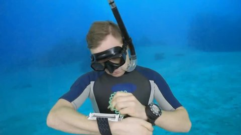 Diving sign- divemaster  writes on the plate and shows ok sign GO UP, ASCENT  also a available on the green screen all of diving signs from course