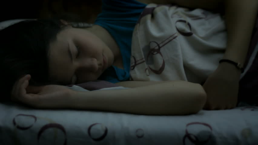 Girl sleeping in the bed late at night, restless