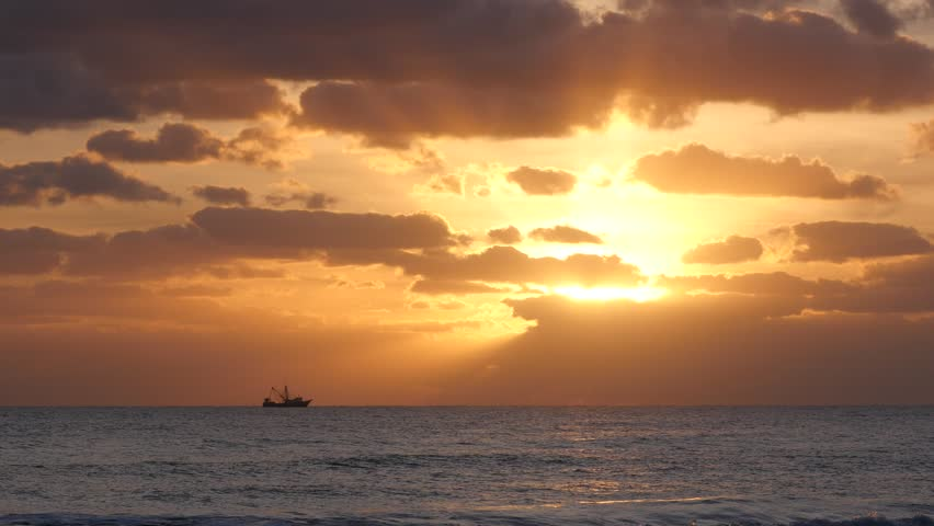 A Shrimp Boat Fishing In The Early Morning During The Sunrise At Cocoa Beach Florida.