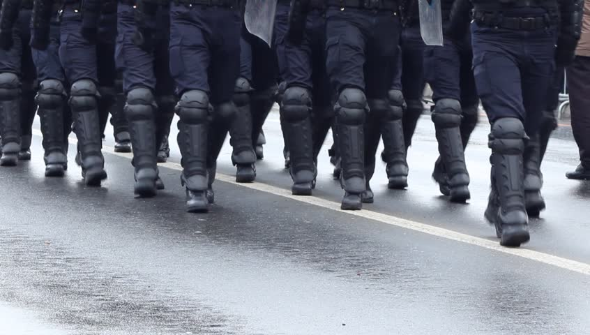 Heavily armored policemen with shields, bats, boots walking in disclpine on a riot public intervention. | Shutterstock HD Video #8937856