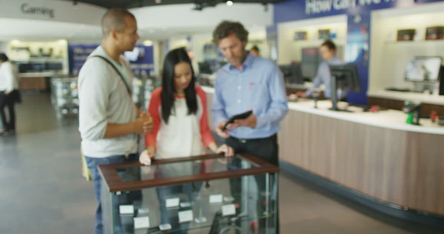 4K Salesman serving customers in consumer electronics store showroom