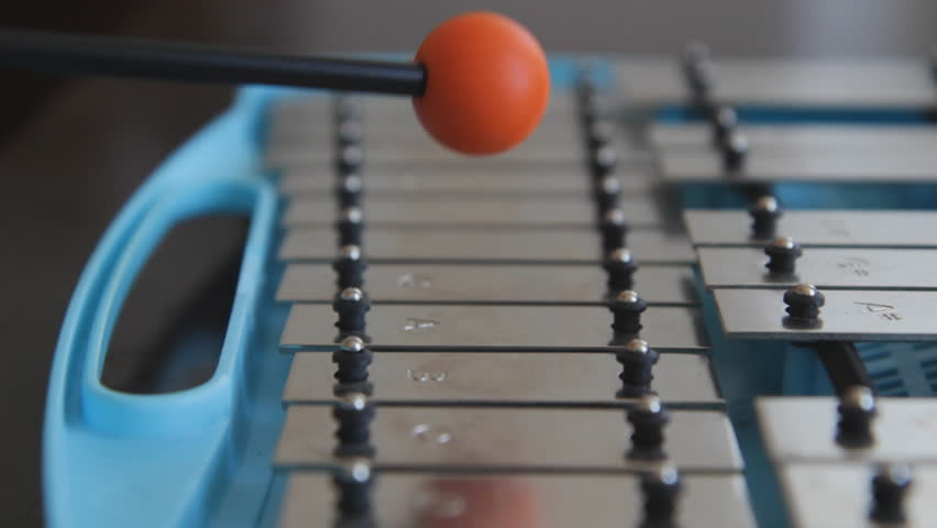 Glockenspiel. Playing a blue children'?s glockenspiel with an orange rubber mallet. Closeup and shallow DOF.