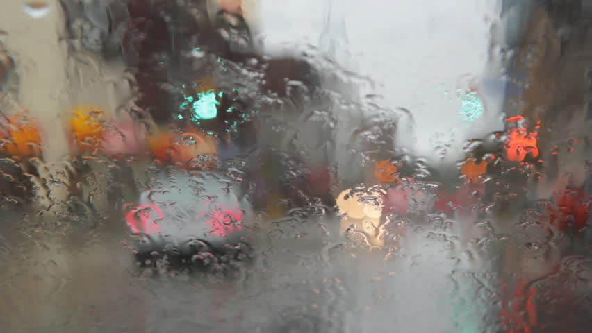 Rainy intersection with pedestrians. View through wet windshield of intersection with pedestrians crossing.