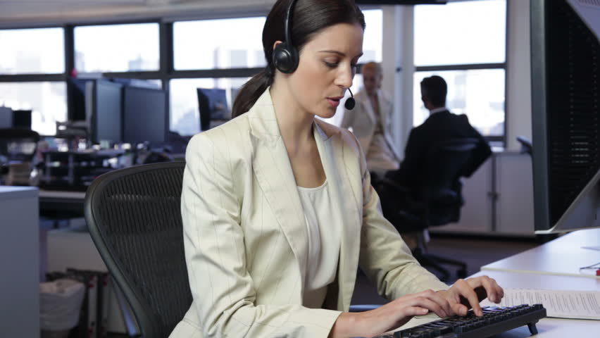 Female call center operator with headphone speaking then looking at camera. | Shutterstock HD Video #8942863