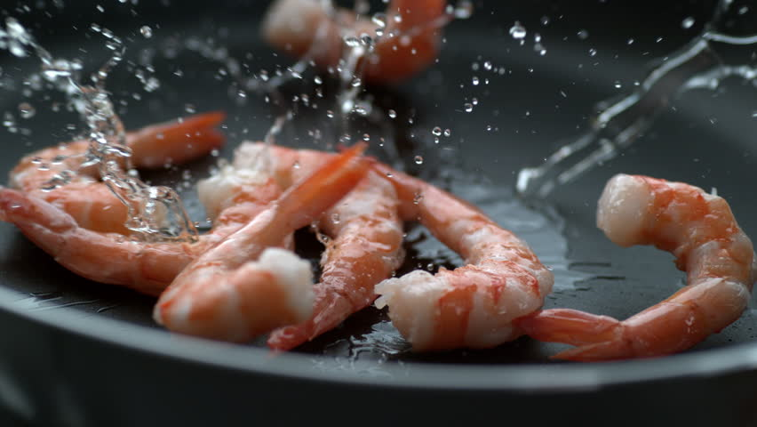 Shrimp splashing into hot oil in frying pan, slow motion; shot on Phantom Flex 4K at 1000 fps