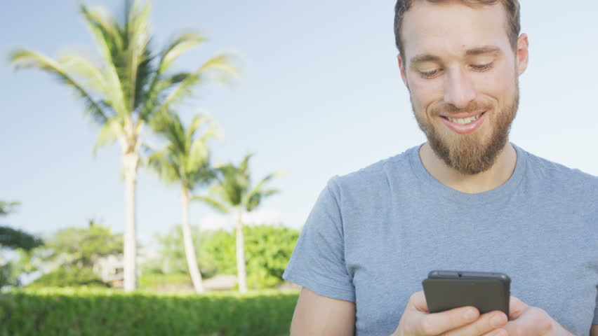 Smartphone man using mobile cell smart phone outdoors in summer. Handsome young casual man using mobile cell phone smiling happy. Urban male hipster. RED EPIC 90 FPS.