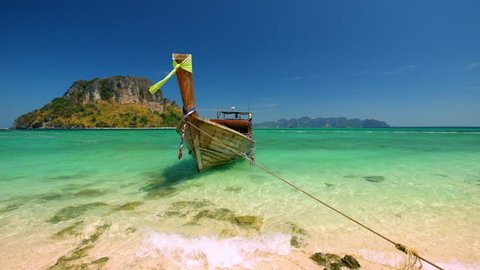 Thai traditional wooden boat with ribbon decoration at ocean shore under blue sky.Thailand tropical beach landscape, Krabi province