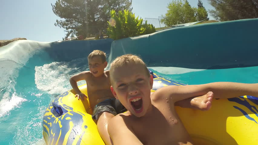 Kids going down a waterslide at waterpark, POV video
