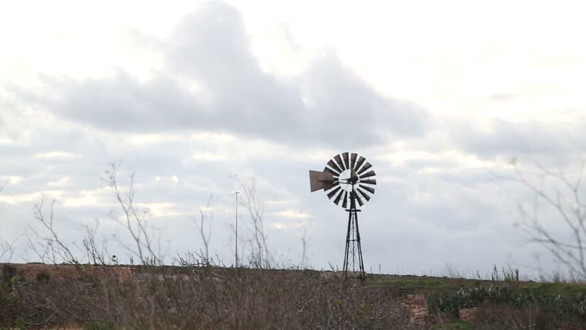 Old iron windpump windmill spinning in nature