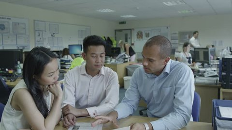 4K An Asian man and woman talk to black male manager in modern office building. Casual business people discussing projects in product manufacturing company. Small business meetings during the day.