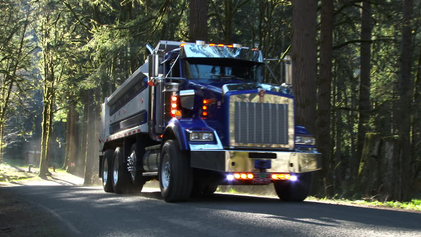 Dump truck driving up forest road in the Pacific Northwest, Oregon.