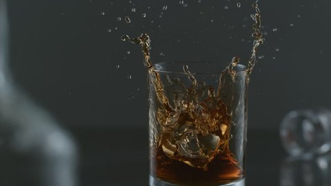 Ice is dropped into glass of whisky in slow motion; shot on Phantom Flex 4K at 1000 fps
