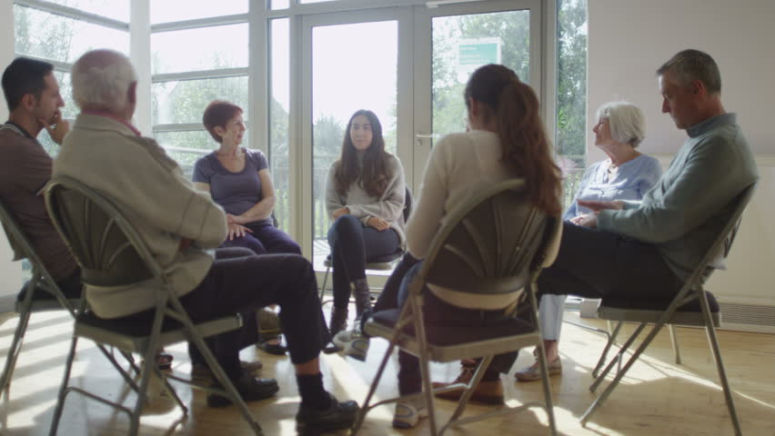 4K People in group therapy session talk about their problems in sunlit room