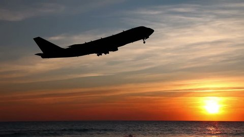 Airplane Take Off Silhouette. Passenger plane flies over the sea at night.