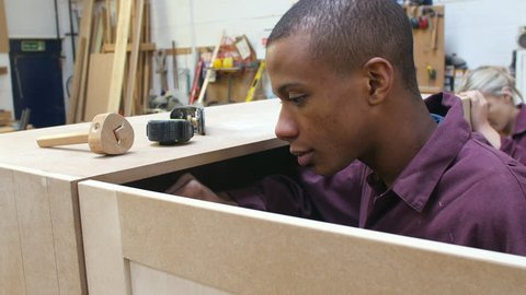 Two apprentices in carpentry workshop working on cabinet.Shot on Sony FS700 at a frame rate of 25fps