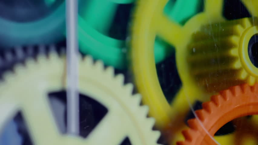 Colorful plastic gears rotate synchronously. Old toy clock mechanism with scratches on the glass. Source: Canon 7D, graded. Clip ID: ax1112c