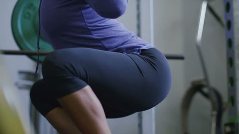 4K Young attractive woman working hard in the gym doing weighted squats, shot on RED EPIC