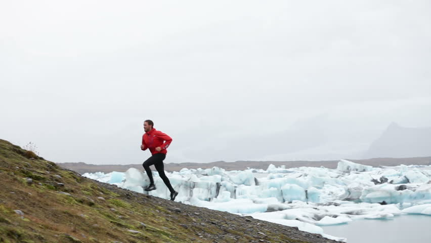 Running man. Trail runner training running uphill in beautiful nature landscape. Fit male athlete jogging and cross country running by icebergs in Jokulsarlon glacial lake in Iceland. | Shutterstock HD Video #9258413