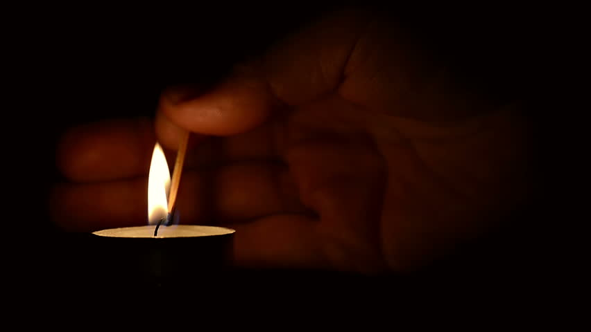 Hand lighting a candle with a match at night with a black background