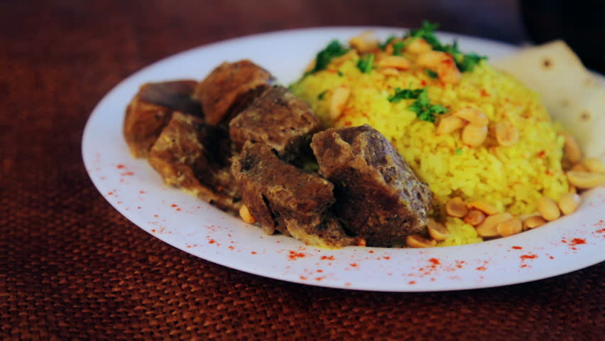 Food, boiled rice with meat and peanuts. Arabic pilaf with meat sauce and peanuts. National Asian and Arabic cuisine. Dish of rice and meat. Pilau, rice, risotto.