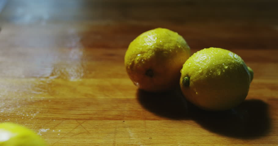 closeup of bunch of wet tomatoes and fresh lemons on wooden