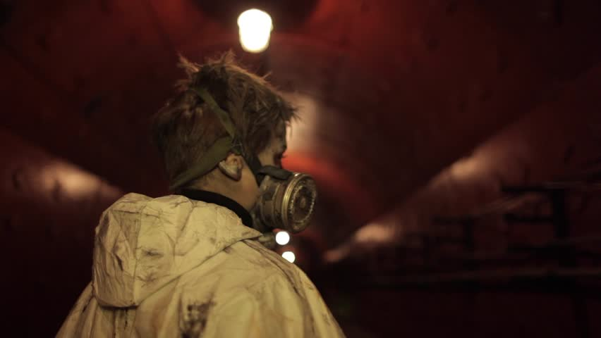 Dirty boy in a gas mask hiding in a bomb shelter. - HD stock footage