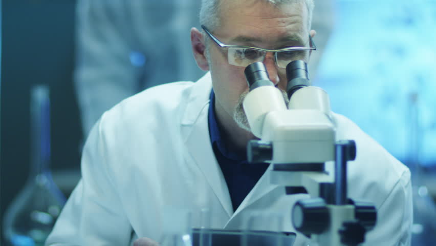 Scientist is Looking through Microscope and Writing Data on Tablet. Shot on RED Cinema Camera in 4K (UHD).