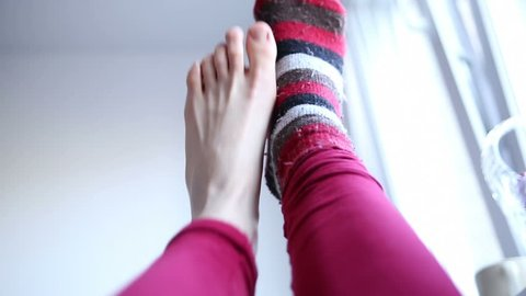 one foot takes off a sock from the over